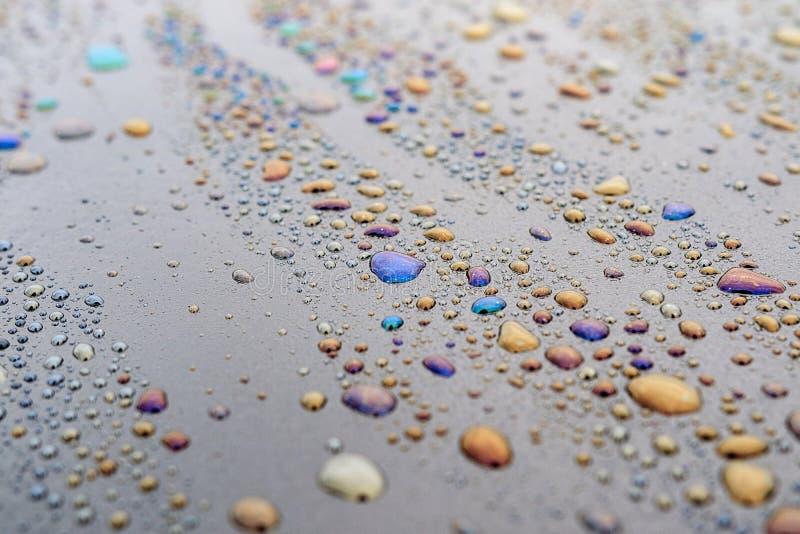 Падения воды смешанные с битумом на темном поверхностном shimmer со всеми цветами стоковое изображение rf
