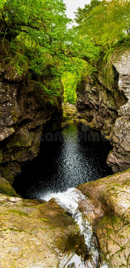 Падения водопада фойе в узком ущелье со старым каменным мостом на Лох-Несс в Шотландии стоковая фотография rf