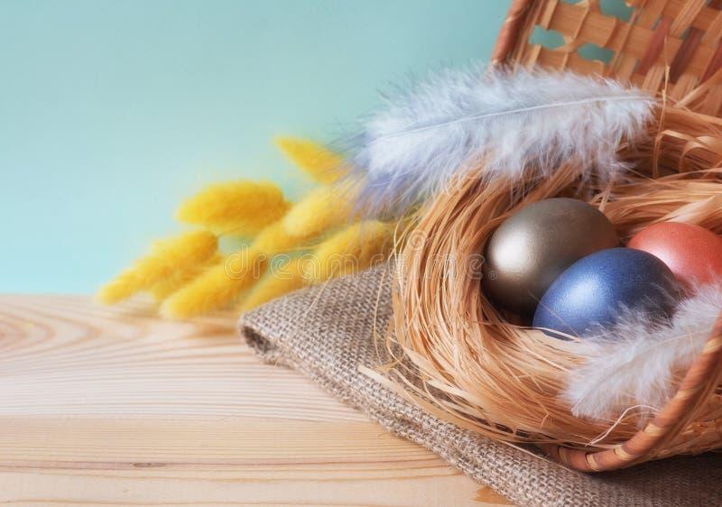 Пасхальные яйца в корзине на деревянной предпосылке стоковые изображения rf