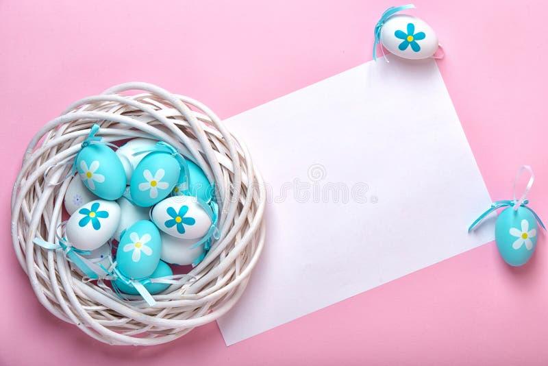 Пасхальные яйца в плетеной корзине и чистом листе бумаги для приветствуя карты пасхи на розовой предпосылке стоковые изображения rf