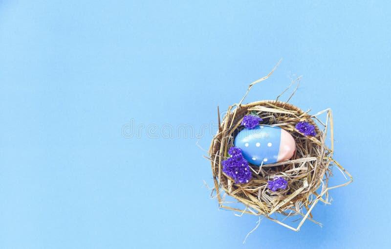 Пасхальные яйца в украшении гнезда корзины с предпосылкой пурпурных цветков statice голубой стоковое фото