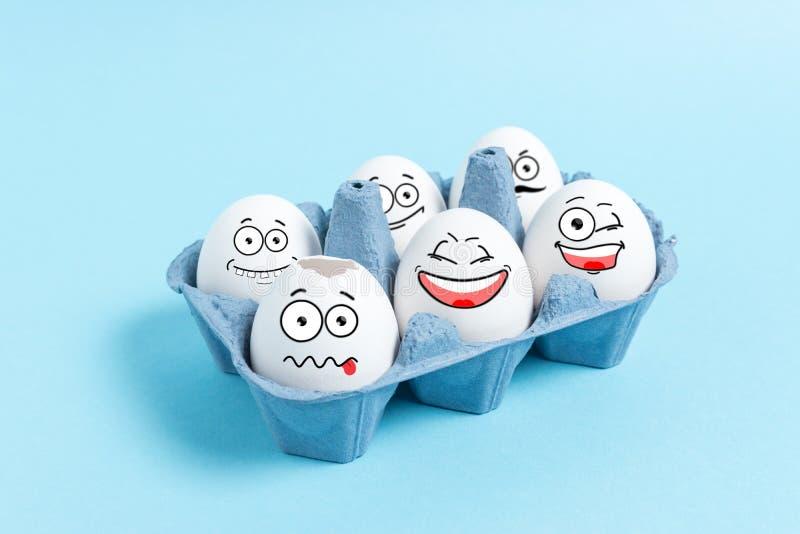 Пасхальные яйца со смешной стороной в подносе коробки на голубой предпосылке Минимальная концепция стоковые фотографии rf