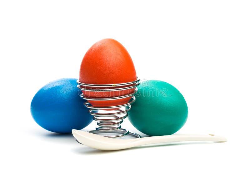 Пасхальное яйцо в стойке яйца с изолированной ложкой стоковые изображения rf