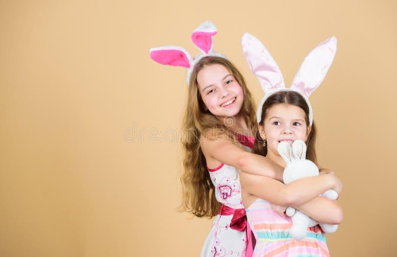 пасха счастливая Девушки зайчика праздника с длинными ушами зайчика Костюм зайчика детей Шаловливые сестры девушек празднуют пасх стоковые изображения rf
