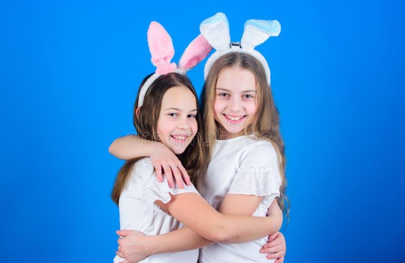 пасха счастливая Девушки зайчика праздника с длинными ушами зайчика обнимают Костюм зайчика пасхи детей Шаловливые сестры девушек стоковое фото