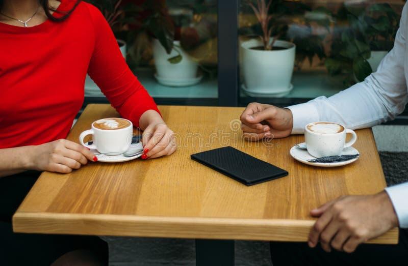 Пара, 2, парень и девушка сидят в кафе, выпивая кофе, 2 чашках капучино на таблице, счета для напитка стоковые фото