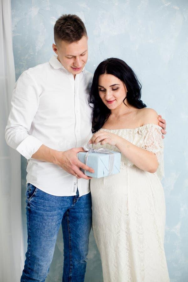 Пара детенышей с беременной женщиной раскрывает подарок стоковое изображение rf