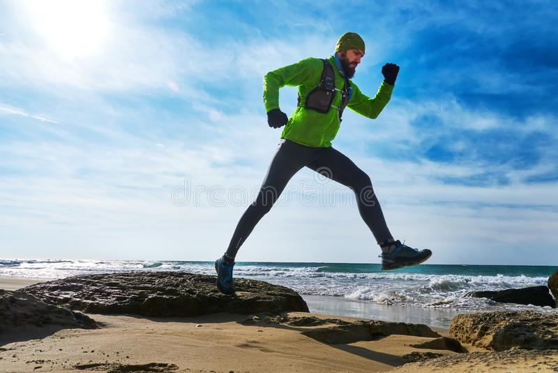 Парень бежит вдоль пляжа замораживание фокуса поля глубины крупного плана действия вышло идущая отмелая тропка ботинок ботинка стоковая фотография