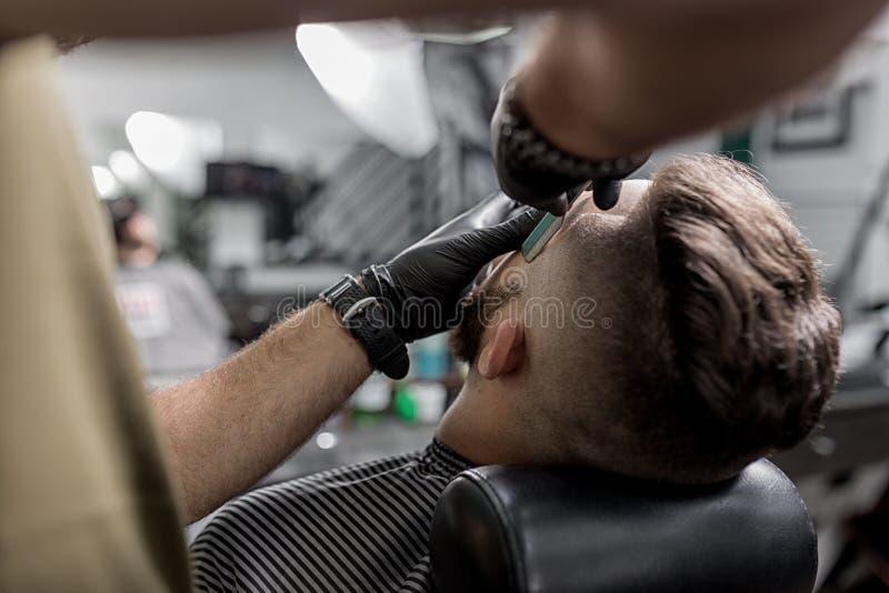Парикмахер в черных перчатках уравновешивает висок зверского бородатого молодого человека с прямой бритвой на парикмахерскае стоковые фото