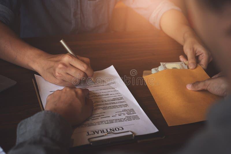 Партнер дает деньги взяткой в конверте другому бизнесмену и указывать на контракт разрешения знака Коррупция и анти- взяточничест стоковая фотография rf