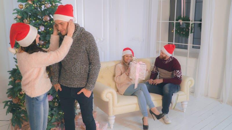 2 пары в влюбленности дома нося в шляпе santa стоковая фотография