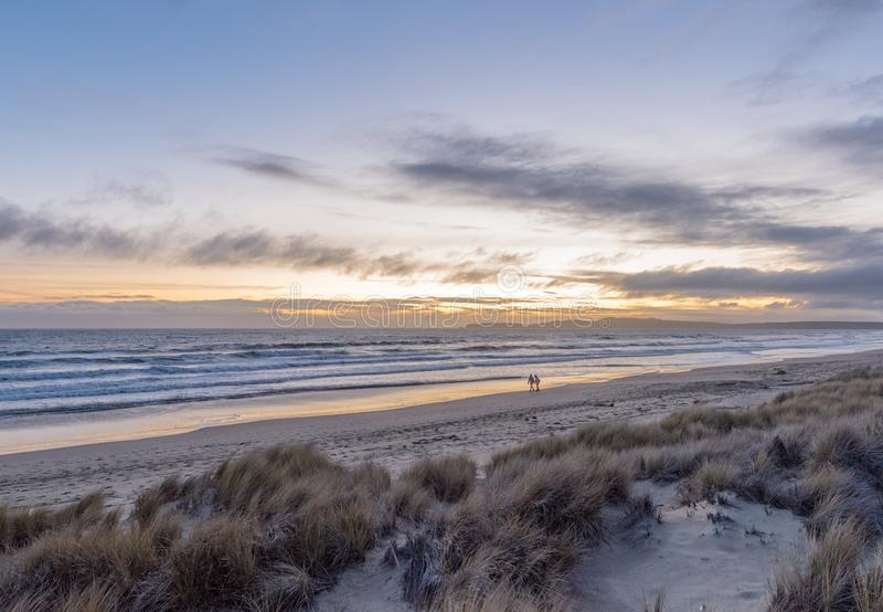 Пары в расстоянии идя вдоль пляжа на заходе солнца стоковое изображение rf