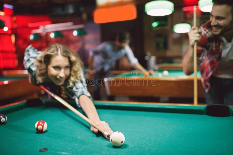 Пары имеют смешное время в женщине бара билльярда играя снукер стоковые фотографии rf