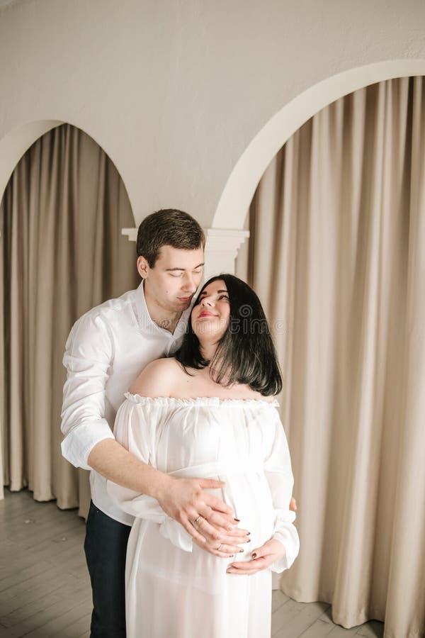 Пары любят обнять беременную женщину семьи стоковое изображение rf