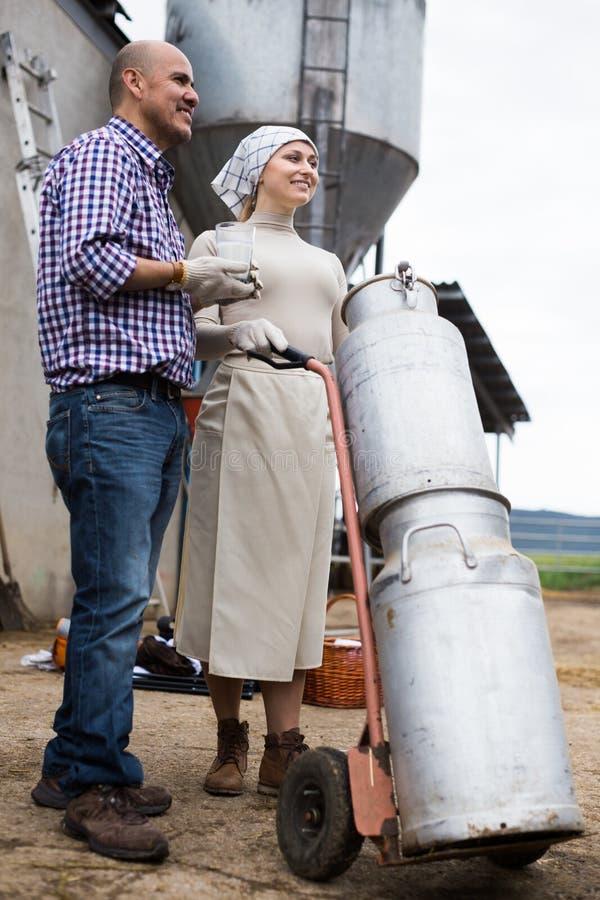 Пары фермеров с чонсервными банками молока стоковое фото