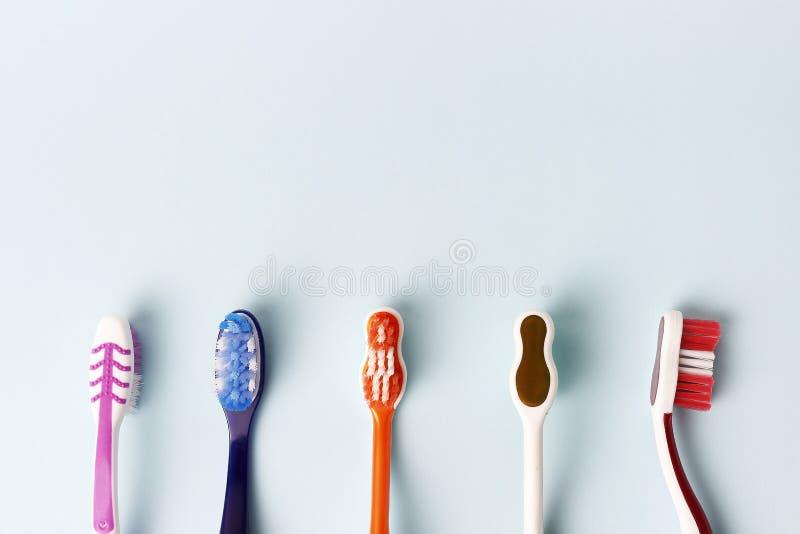 Пестротканые зубные щетки на голубой предпосылке, космосе экземпляра стоковые изображения
