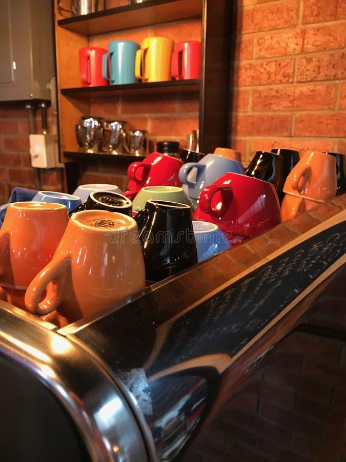 Пестротканые чашки кофе и чая расположенные на машине кофе против кирпичной стены стоковая фотография rf