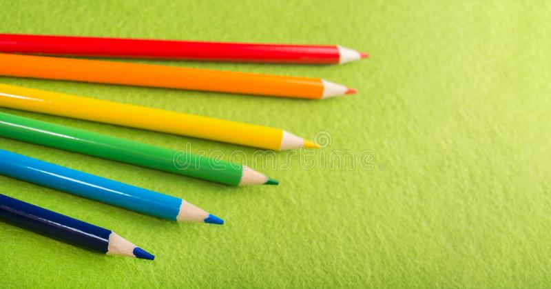 6 пестротканых карандашей на зеленой чувствуемой предпосылке Различные покрашенные карандаши с космосом для текста задняя школа к стоковые изображения