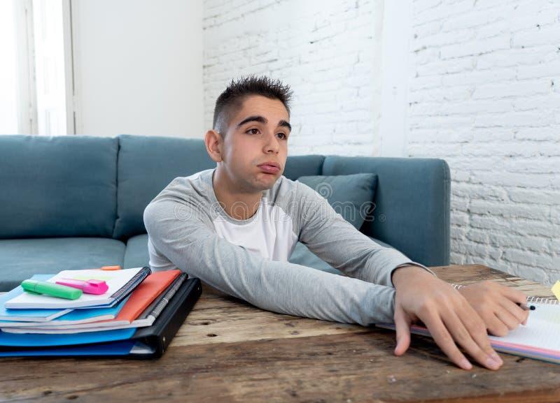 Перегружанный и уставший человек студента средней школы изучая домашнее чувство подавленное и отчаянное стоковое изображение