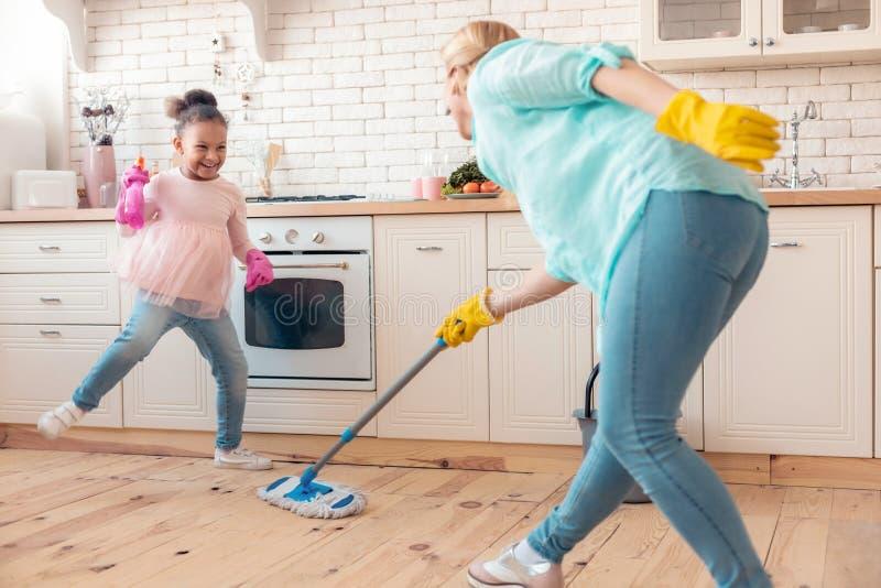 Перчатки матери и дочери нося mopping пол в кухне стоковые фото