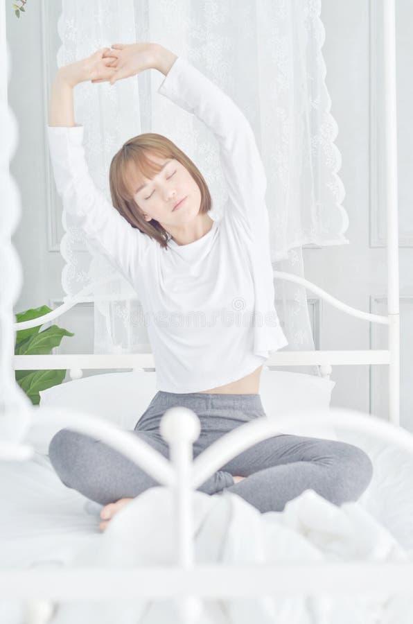 Пижамы женской одежды белые в кровати стоковые изображения rf