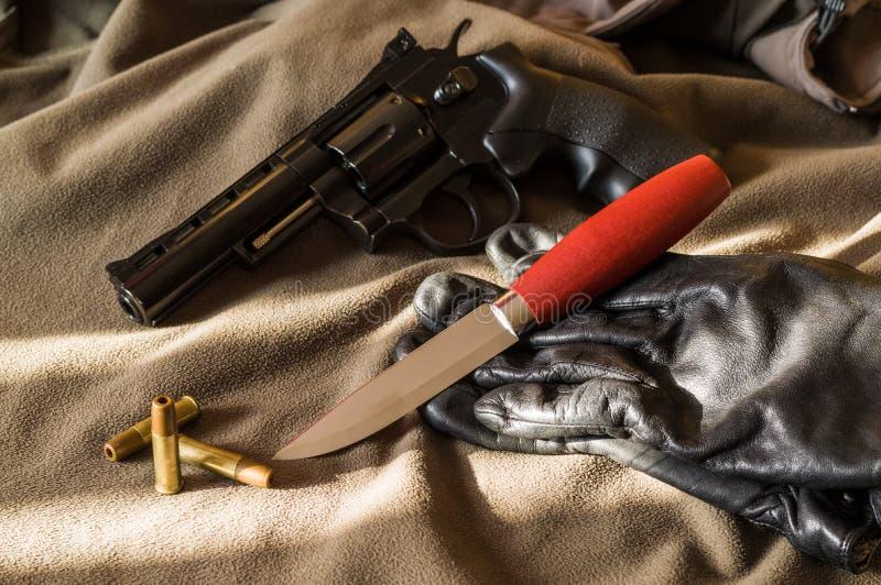 Пистолет, нож и перчатки Пистолет и пули светлая тень стоковое изображение