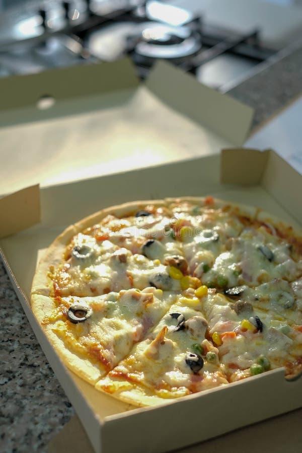 Пицца в коробке около плиты в кухне стоковые фотографии rf