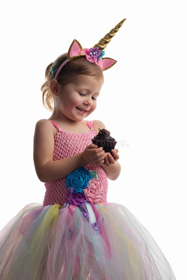 Пирожное удерживания маленькой девочки на белизне стоковое фото rf
