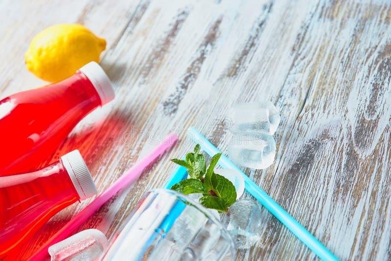 Пластиковые бутылки с ягодами, освежающим напитком разбросанные кубы льда и выпивая соломы на предпосылке затрапезное деревянного стоковая фотография