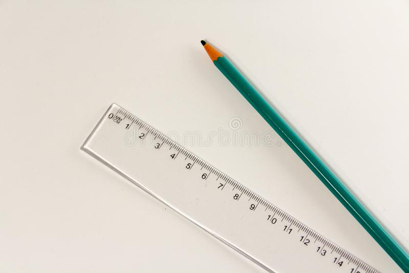 Пластиковый правитель и деревянный карандаш на белизне стоковое изображение