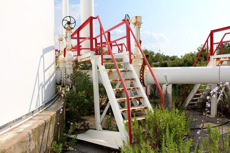 Платформа металла с заржаветыми шагами окруженная с трубопроводами и клапанами на получившемся отказ промышленном комплексе вполн стоковое изображение