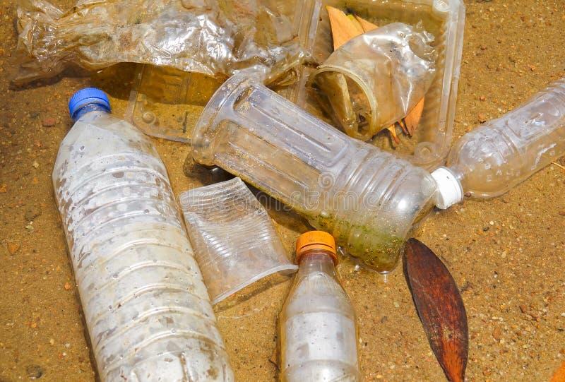 Плохая экологическая привычка неправильного избавления не-biodegradable чашек и бутылок PVC в озере Селективный фокус стоковое фото