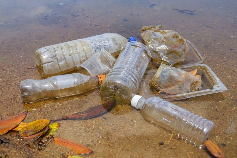 Плохая экологическая привычка неправильного избавления не-biodegradable чашек и бутылок PVC в озере Селективный фокус стоковое изображение