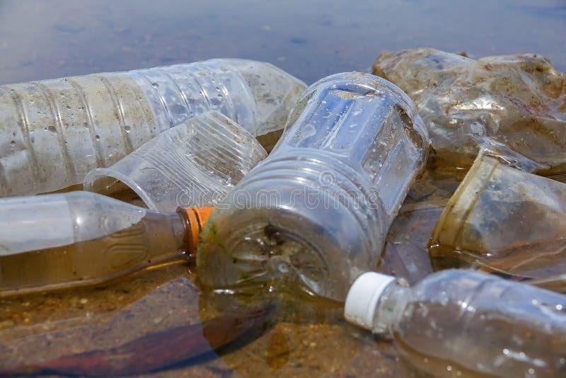 Плохая экологическая привычка неправильного избавления не-biodegradable чашек и бутылок PVC в озере Селективный фокус стоковое изображение rf