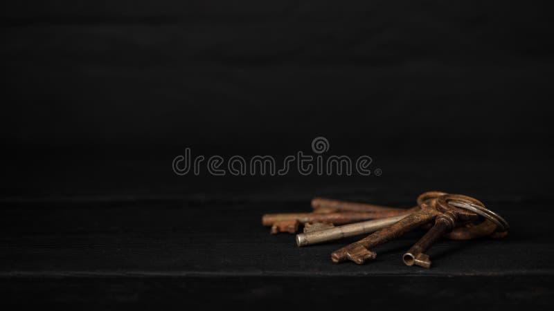 Пук старых ключей на таблице, низкого ключа металла Тема собирать, винтажное украшение, концепция безопасности стоковые изображения rf