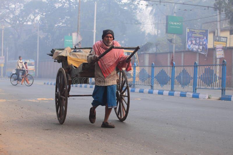 Пулер рикши идет в улицы в туманном утре стоковая фотография rf
