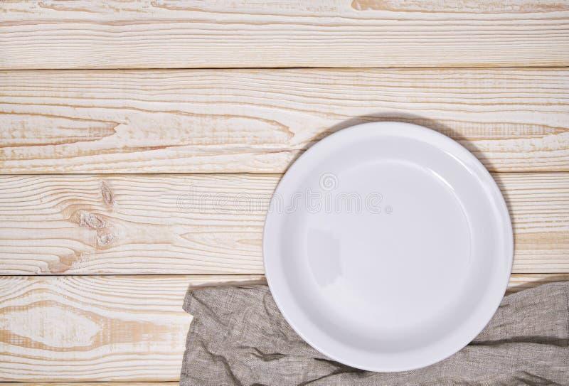 Пустая белая плита и серая салфетка на деревянной предпосылке, взгляд сверху стоковое изображение rf