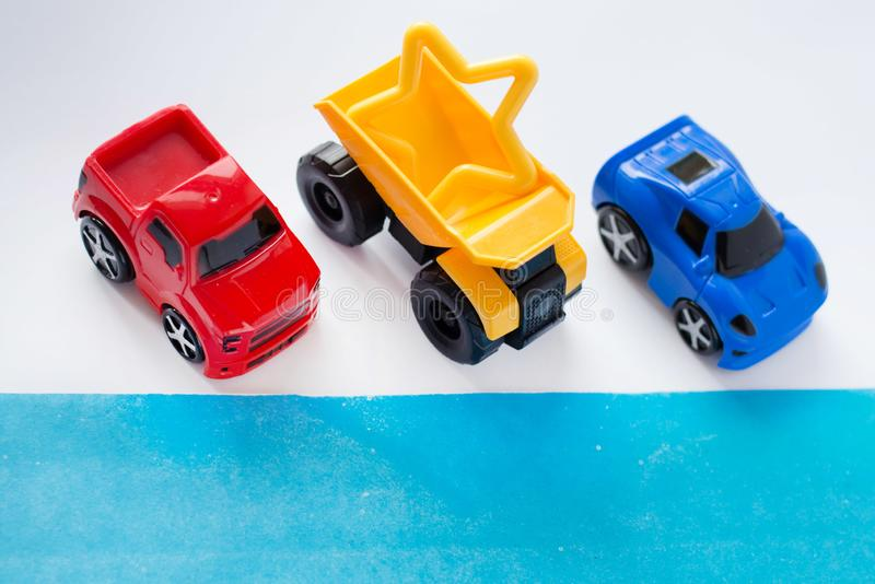 Пустая белая предпосылка украшает с миниатюрными красочными автомобилями Плоское положение, взгляд сверху стоковые фотографии rf