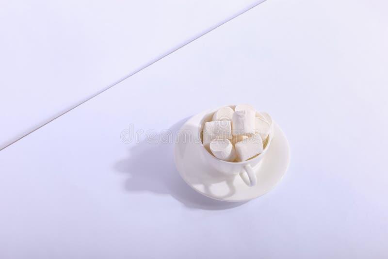 Пустая керамическая чашка с зефирами на поддоннике, на белой предпосылке Трудная тень от солнца, концепции утра стоковое фото rf