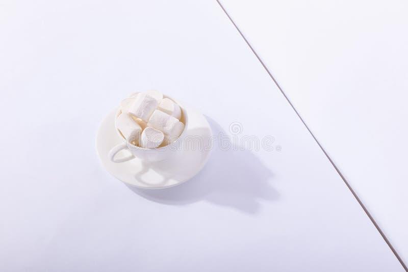 Пустая керамическая чашка с зефирами на поддоннике, на белой предпосылке Трудная тень от солнца, концепции утра стоковая фотография rf