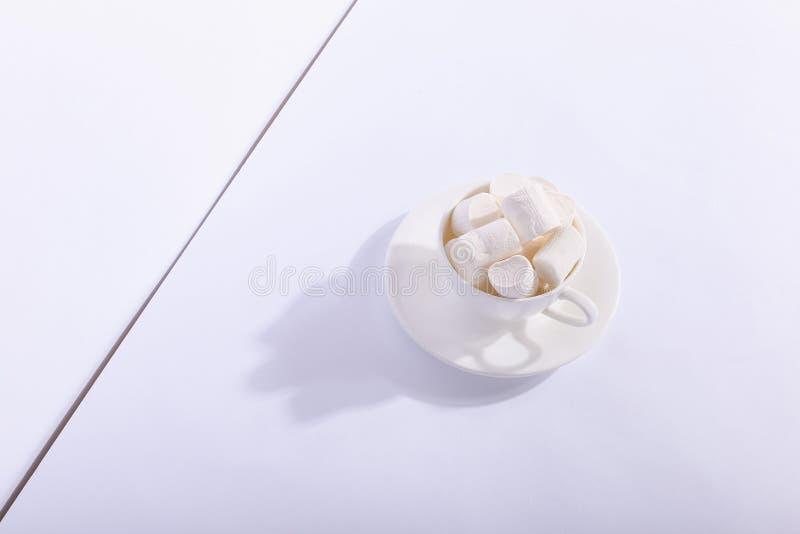 Пустая керамическая чашка с зефирами на поддоннике, на белой предпосылке Трудная тень от солнца, концепции утра стоковое изображение rf