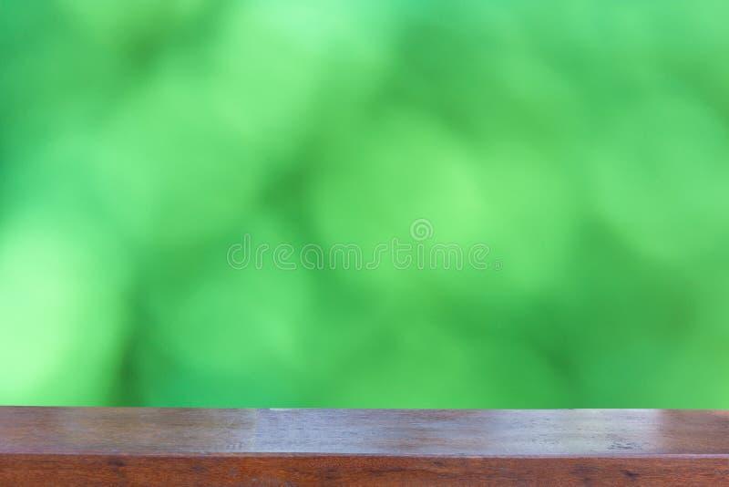 Пустая деревянная столешница на запачканной конспектом зеленой предпосылке bokeh стоковые изображения rf