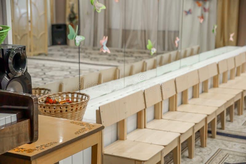 Пустая строка деревянных стульев детей в музыкальной комнате перед торжеством в партии концертного зала ждать стоковое изображение rf