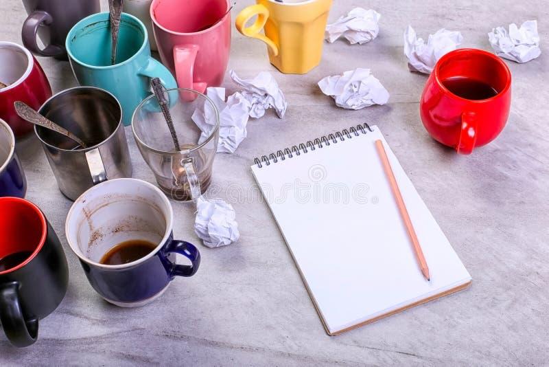 Пустые грязные кофейные чашки, другие цвета на таблице и тетрадь для записи письма Допинг кофеина концепции, недостаток энергии стоковая фотография rf