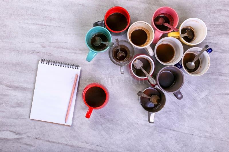 Пустые грязные кофейные чашки, другие цвета на таблице и тетрадь для записи письма Допинг кофеина концепции, недостаток энергии стоковая фотография