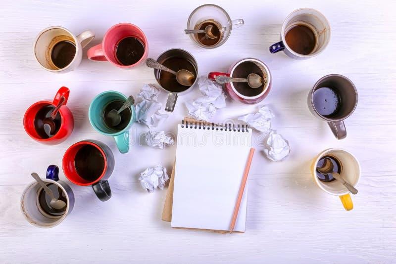 Пустые грязные кофейные чашки, другие цвета на таблице и тетрадь для записи письма Допинг кофеина концепции, недостаток энергии стоковое изображение rf
