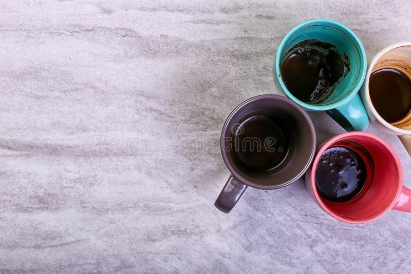 Пустые грязные кофейные чашки других цветов на таблице Концепция допинга кофеина, недостаток энергии и длинное ожидание скопируйт стоковое изображение rf