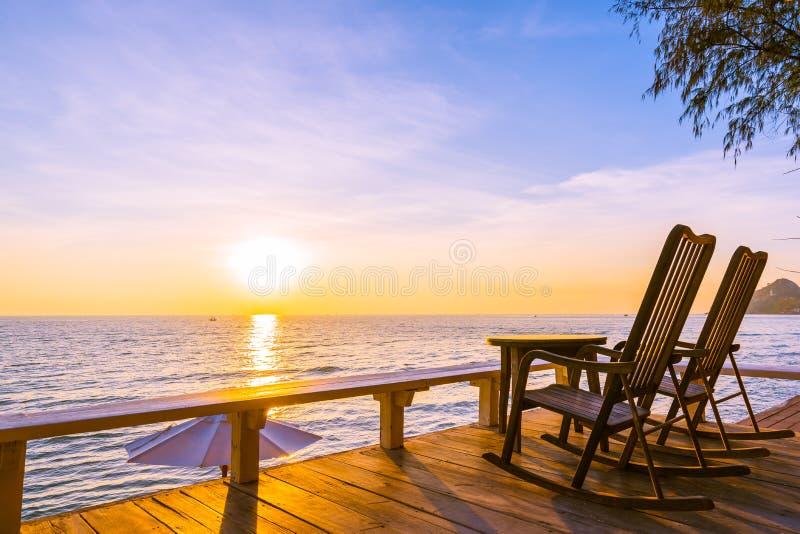 Пустые деревянные стул и таблица на на открытом воздухе патио с красивыми тропическими пляжем и морем стоковые фотографии rf