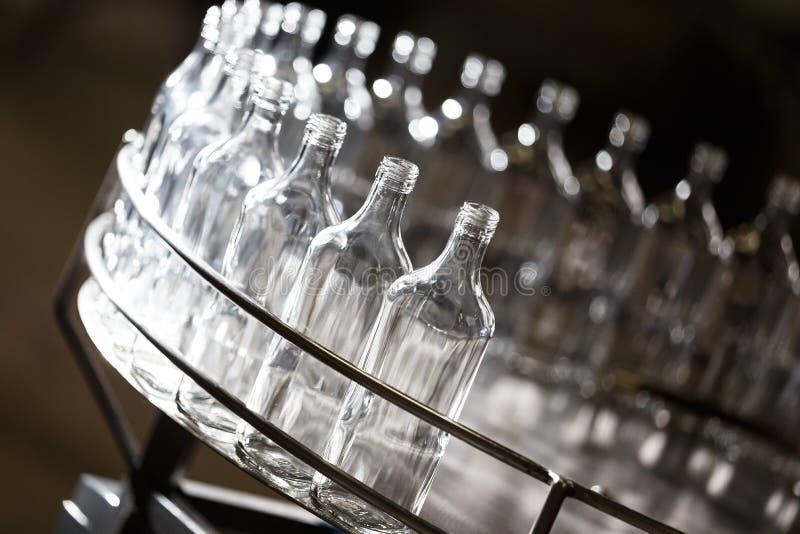 Пустые стеклянные бутылки на транспортере Фабрика для разливая по бутылкам алкогольных напитков стоковая фотография rf