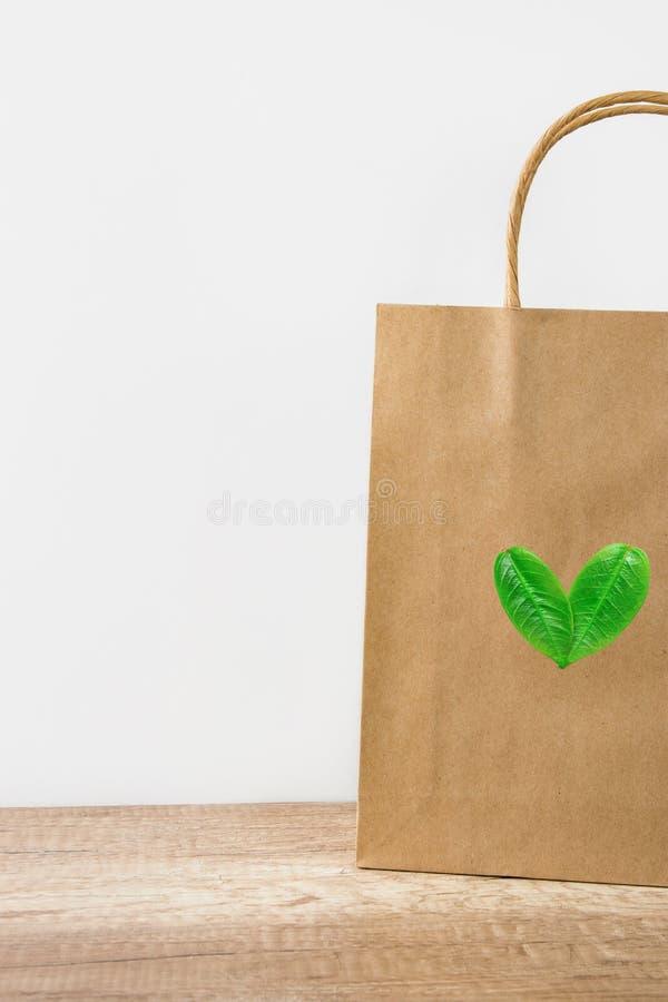 Пустой коричневый бумажный мешок ремесла на белой предпосылке стены Логотип сердца от листьев Стиль природы дружелюбный Экологиче стоковое изображение